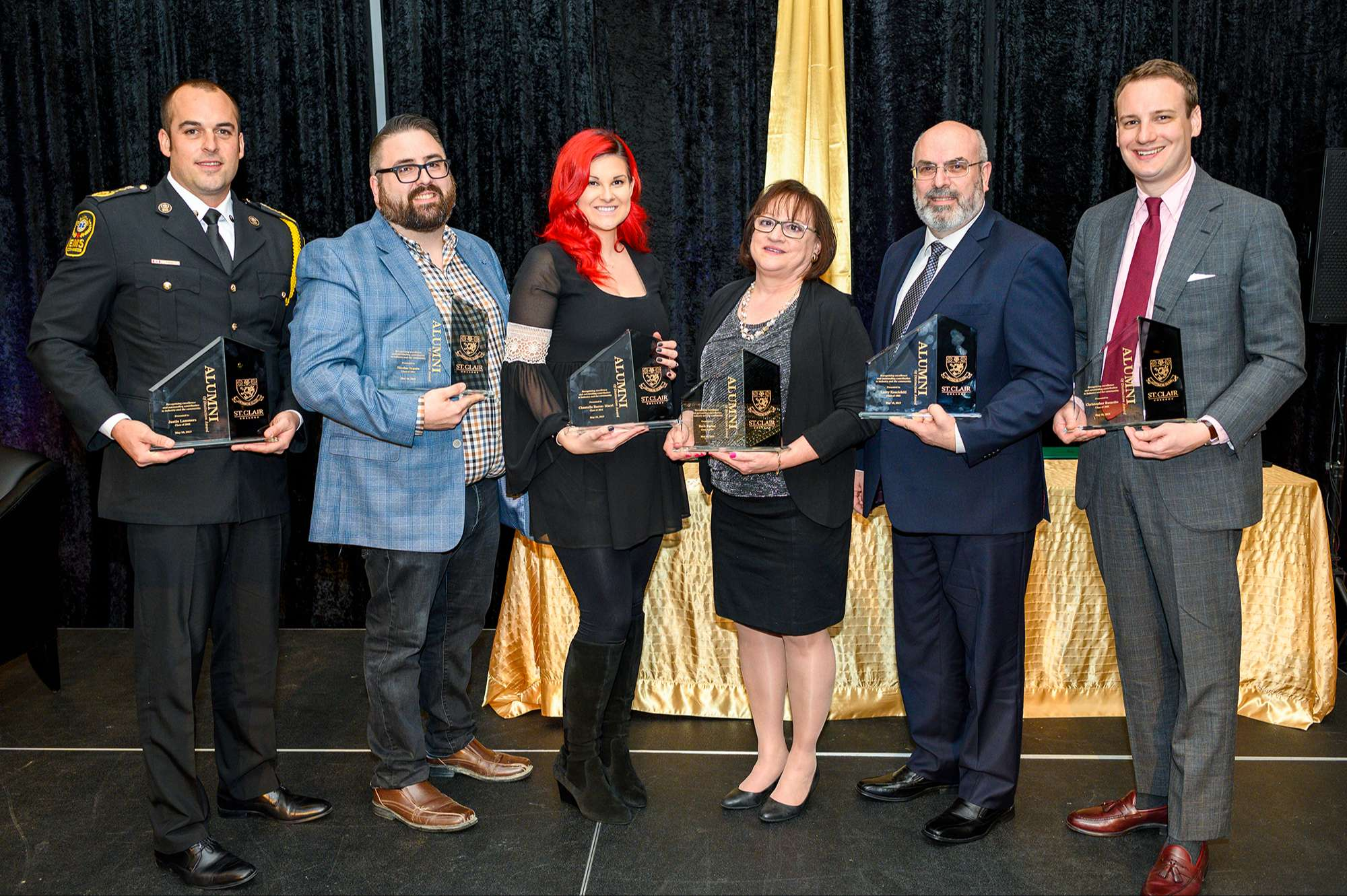 The 2019 alumni of distinction recipients with their trophy's.