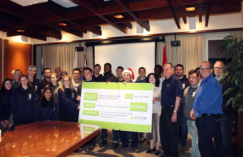 Students presenting cheque to Windsor Goodfellows